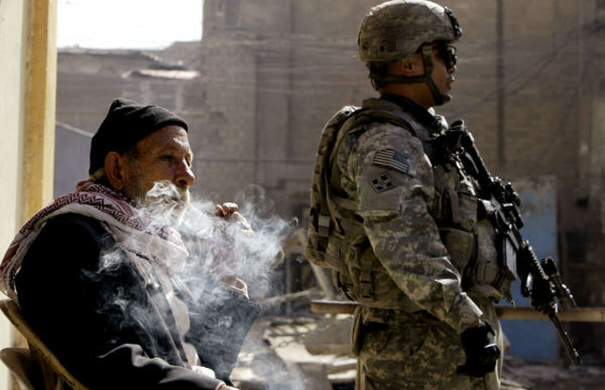 An Iraqi fishmonger smokes as a U.S. soldier stands guard at the Shuhada fish market Thursday. The market is located in a Sunni neighborhood.