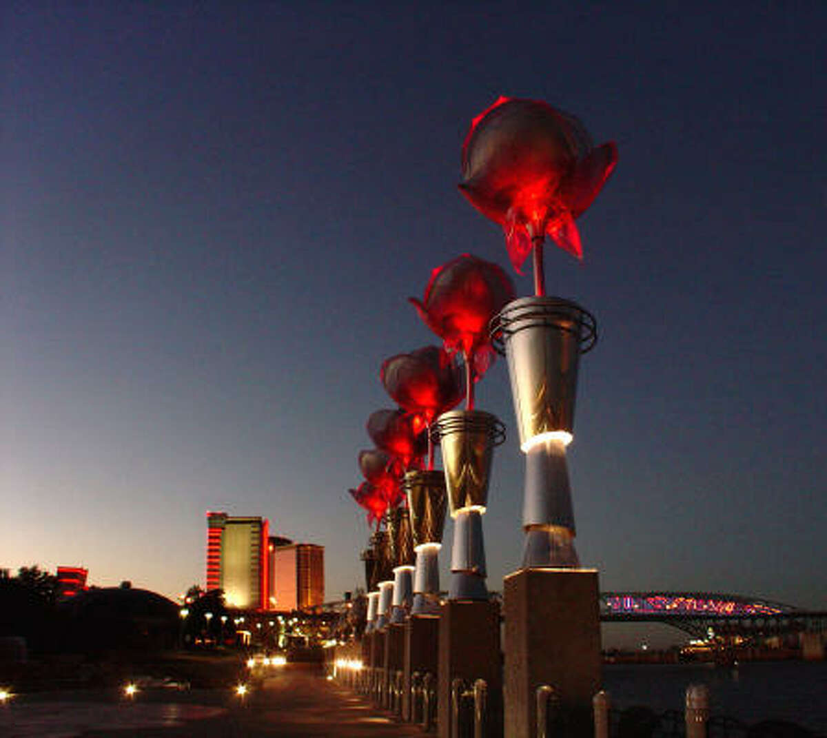 Illuminated steel roses tower 35 feet above RiverView Park along the Red River in Shreveport, La. Bossier City is on the east side of the river.