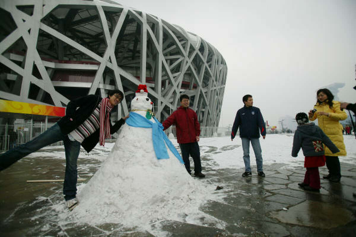 Residents pose for a photo next to a snowman outside the Bird's Nest on Wednesday in Beijing.