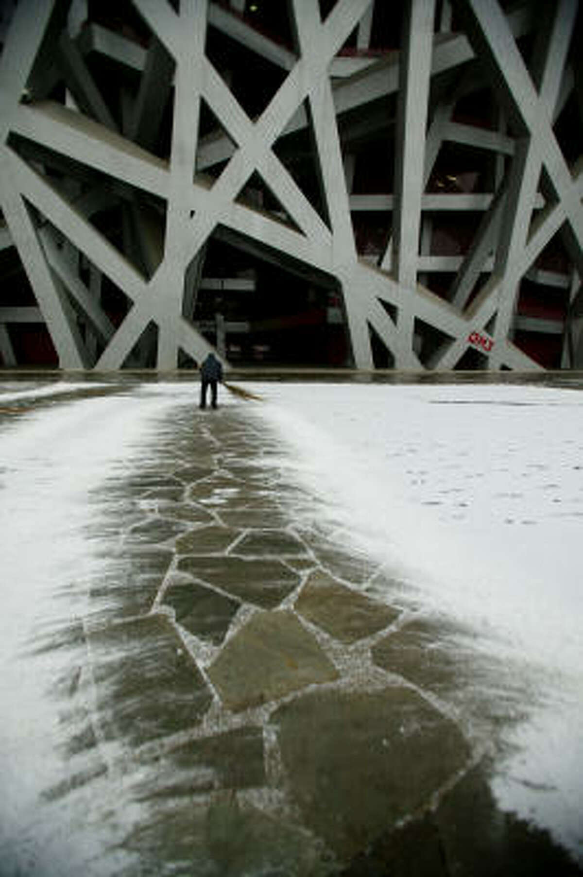 A cleaner sweeps snow outside the Bird's Nest on Wednesday in Beijing.