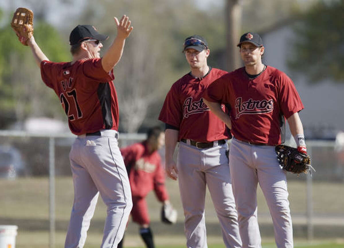 Infielder Geoff Blum throws his arms in the air while talking with Chris Johnson and Aaron Boone during spring training at Osceola County Stadium.