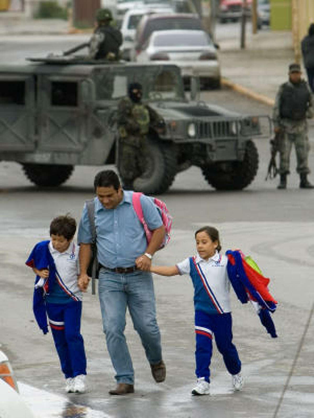 Un hombre busca un lugar seguro luego de buscar a dos niños de la escuela primaria Carrillo Puerto, cerca de donde fueron los enfrentamientos armados.