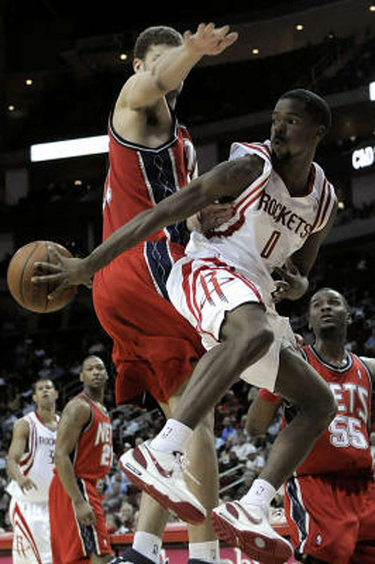 Aaron Brooks (0) passes the ball behind Nets center Brook Lopez during the second half.