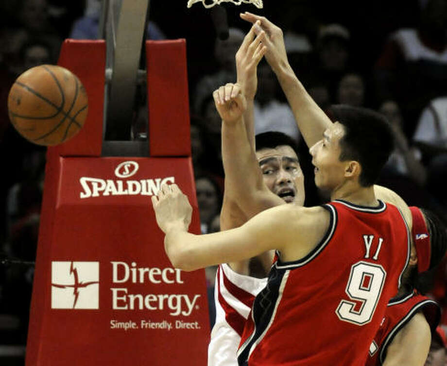 Nets forward Yi Jianlian battles Chinese National Team teammate and Rockets center Yao Ming for a loose ball in the first half. Photo: Pat Sullivan, AP