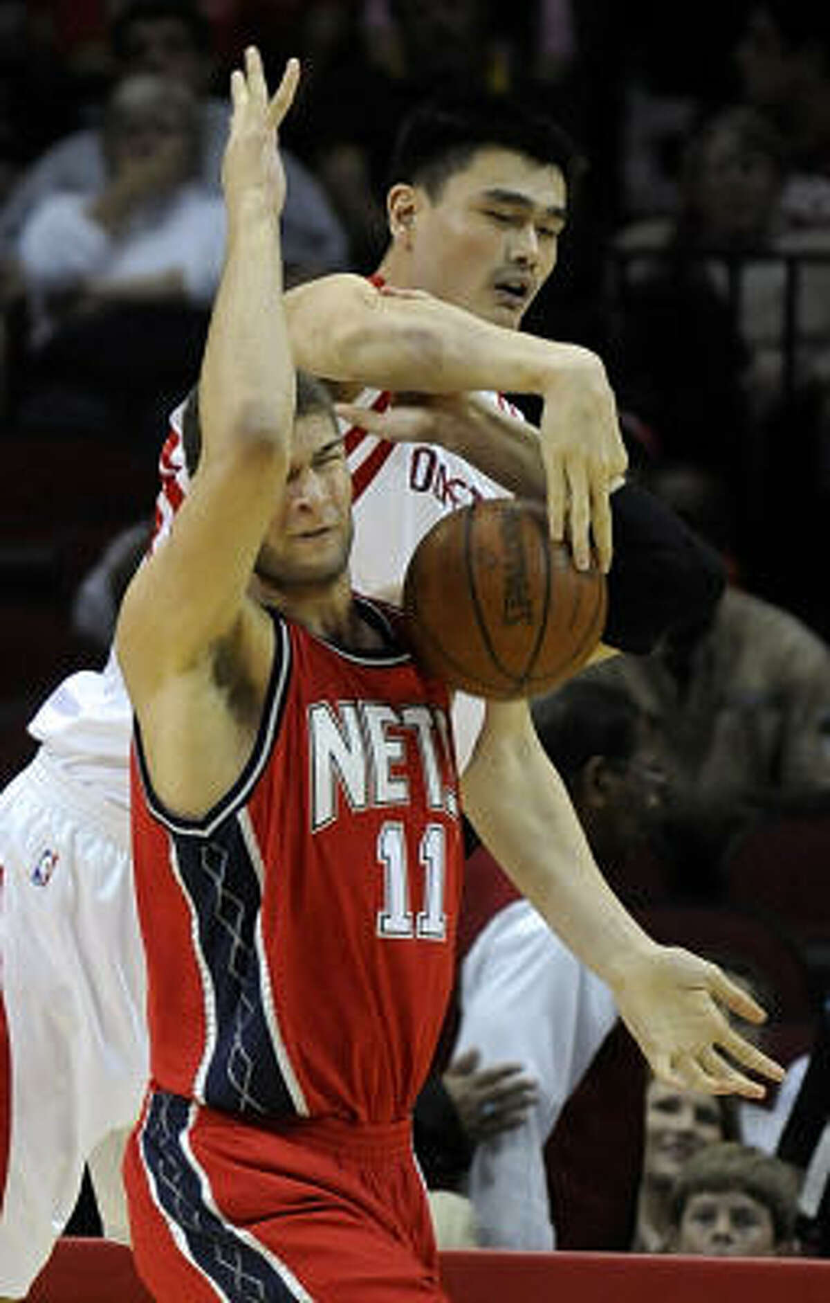 Yao Ming, back, battles Nets center Brook Lopez for a loose ball in the first half.