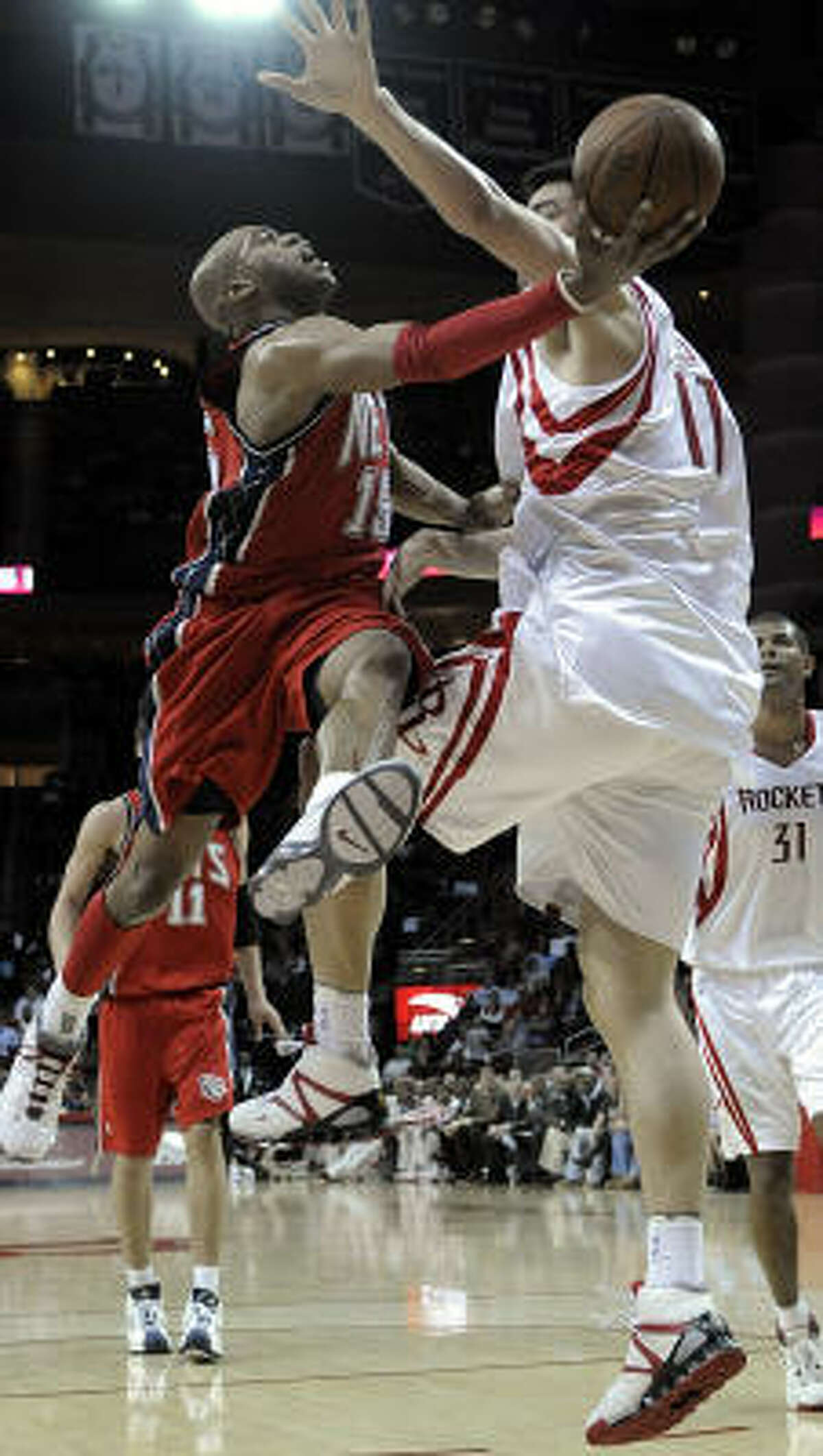 Nets guard Vince Carter, left, drives past Yao Ming on his way to the basket in the first half.