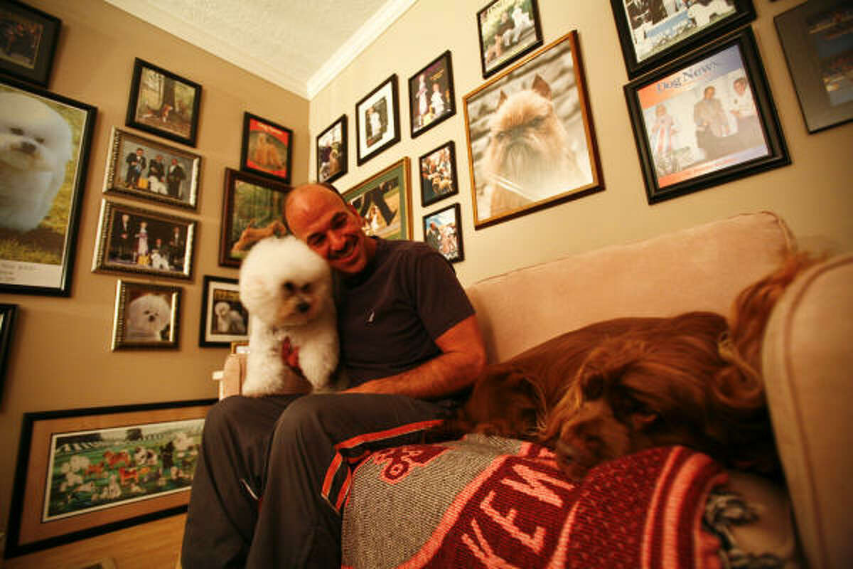 Scott Sommer holds J.R., the 2001 Westminster Dog Show Champion, as Stump rests on the sofa.