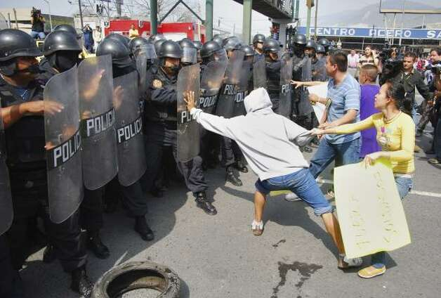 Protesters taunt riot police in the northern industrial city of Monterrey, Mexico, on Tuesday. Photo: STR, AP