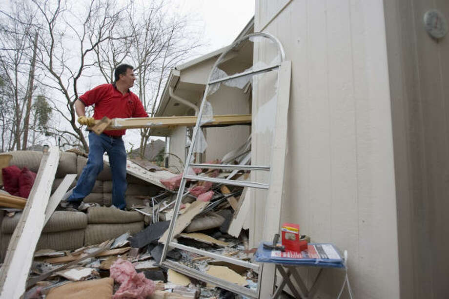 Rick Alspaugh of Alspaugh's Ace Hardware places a board over the gaping hole at the front of the home of Raul and Lisa Valles on Tuesday in Atoscocita.  An SUV plowed into the home injuring the husband and wife who were seated on a couch, at left. Photo: Sharon Steinmann, Chronicle