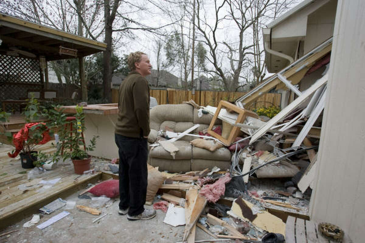 Sparky Nolan, president of the Kingwood Chamber of Commerce, assesses the damage at the home of Raul and Lisa Valles on Tuesday in Atoscocita.
