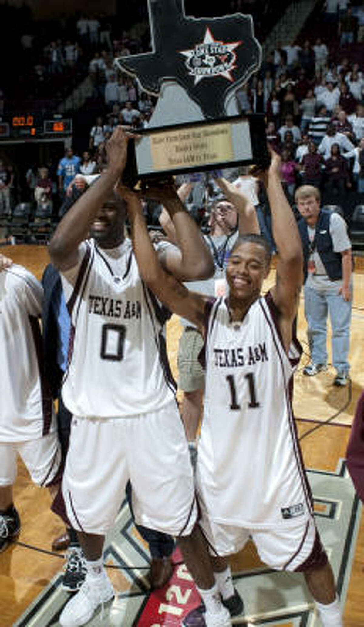 Texas A&M's Bryan Davis (0) and B.J. Holmes celebrate with the Lone Star Showdown trophy after beating Texas 81-66 in Monday night's game at Reed Arena in College Station.