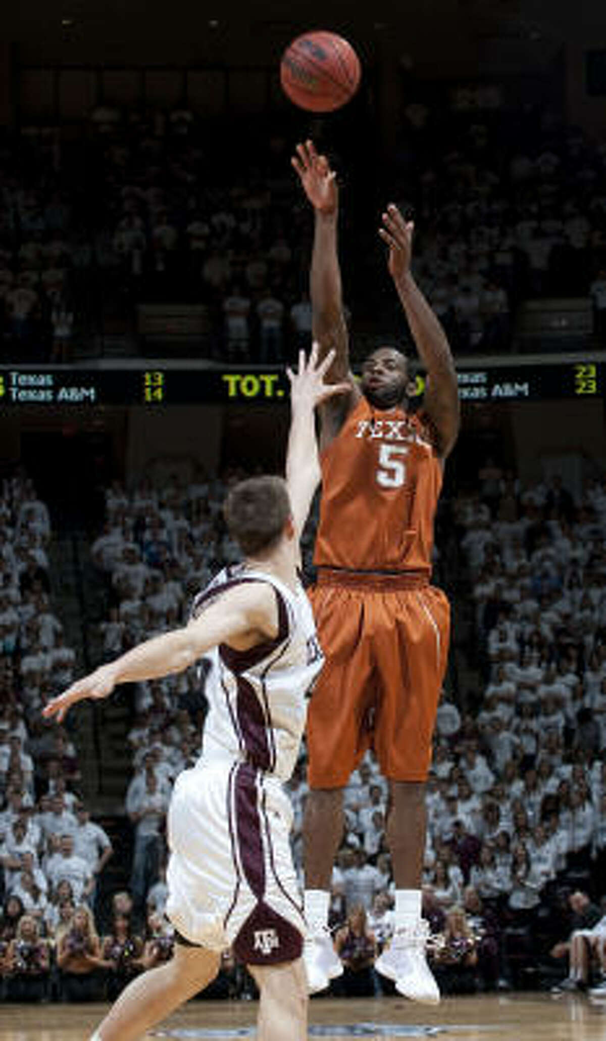 Texas' Damion James (5) shoots a 3-pointer over Texas A&M's Nathan Walkup during the second half.