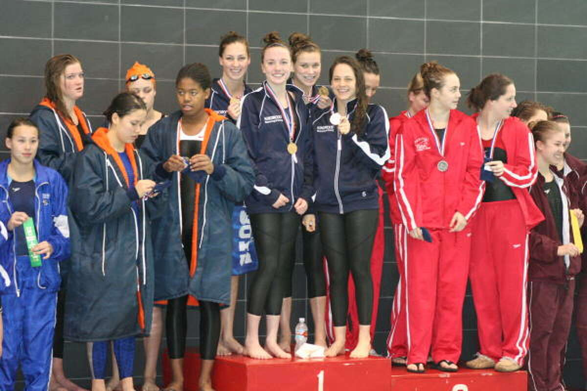 Seven Lakes, Kingwood and Memorial swim teams receive their medals. Kingwood's girls won all three relays and six of the eight individual events to amass 172 points. Seven Lakes took second with 70 points.