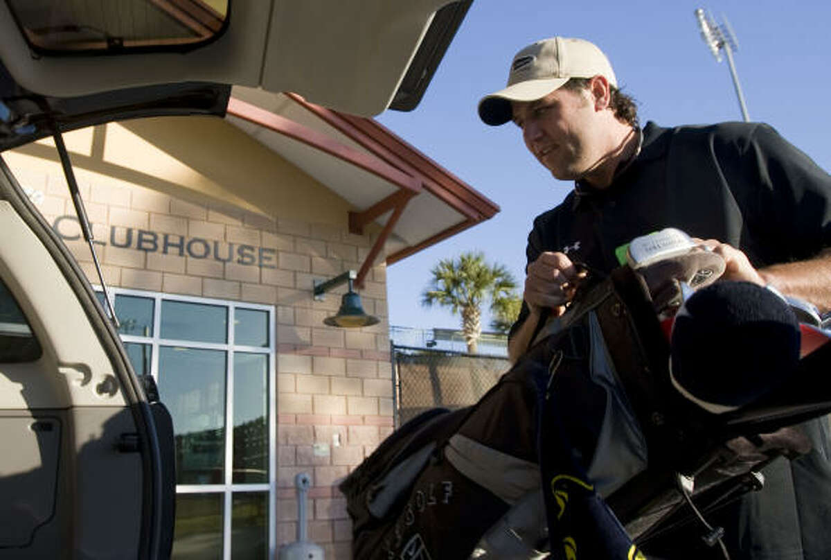 Lance Berkman places a bag of golf clubs in his vehicle after arriving to Astros spring training Monday at Osceola County Stadium in Kissimmee, Fla.