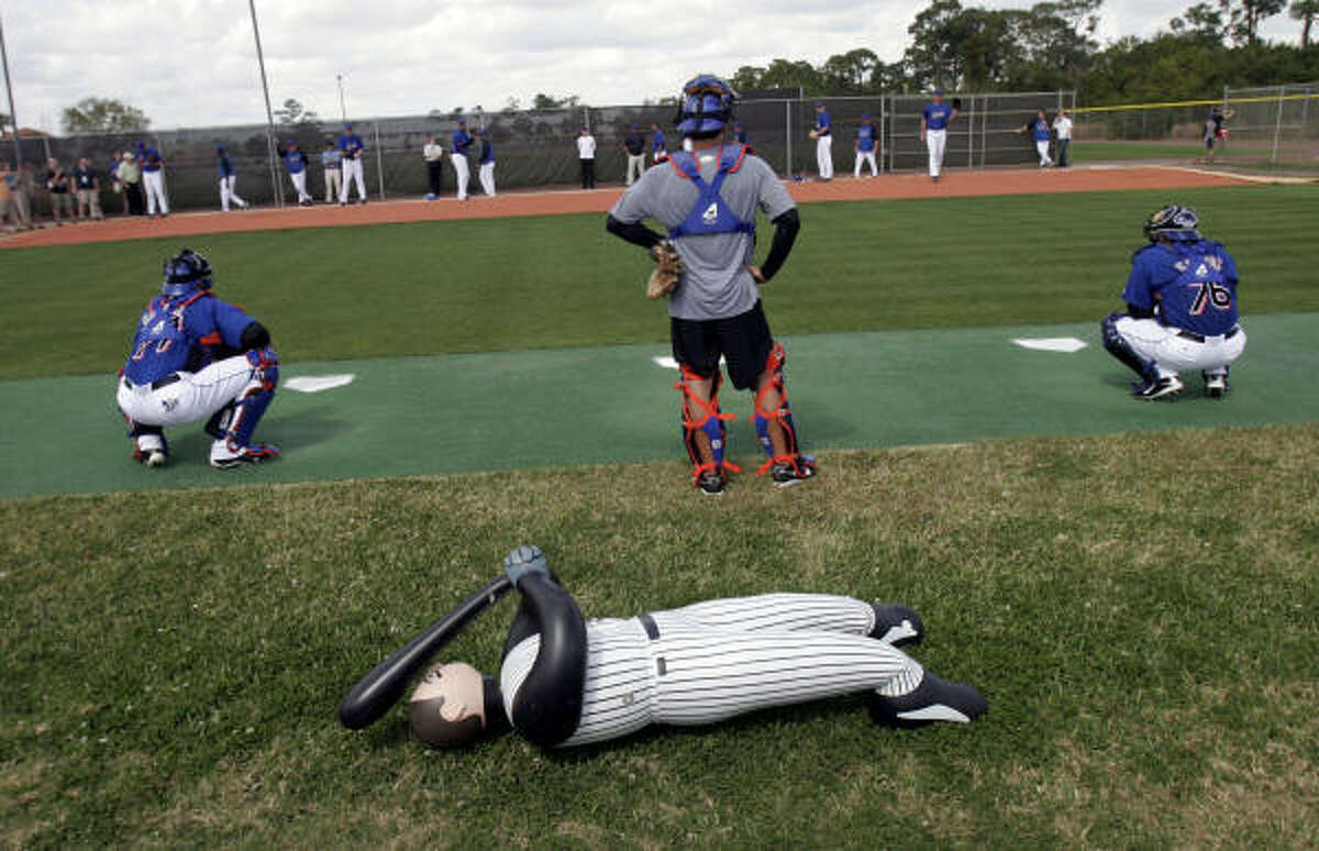 An unused blowup stand-in batter lies on the field as New York Mets pitchers and catchers work out during spring training.