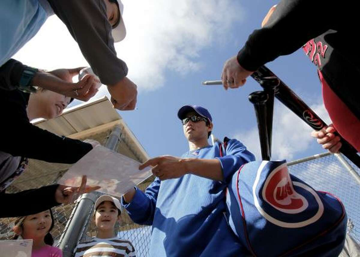 Chicago Cubs' So Taguchi signs some autographs during spring training.