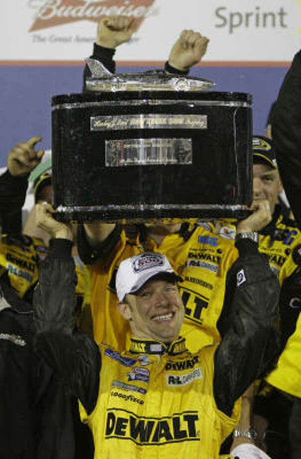 Matt Kenseth holds up the trophy as he celebrates with his crew in victory lane after winning the rain-shortened Daytona 500. Photo: John Raoux, AP