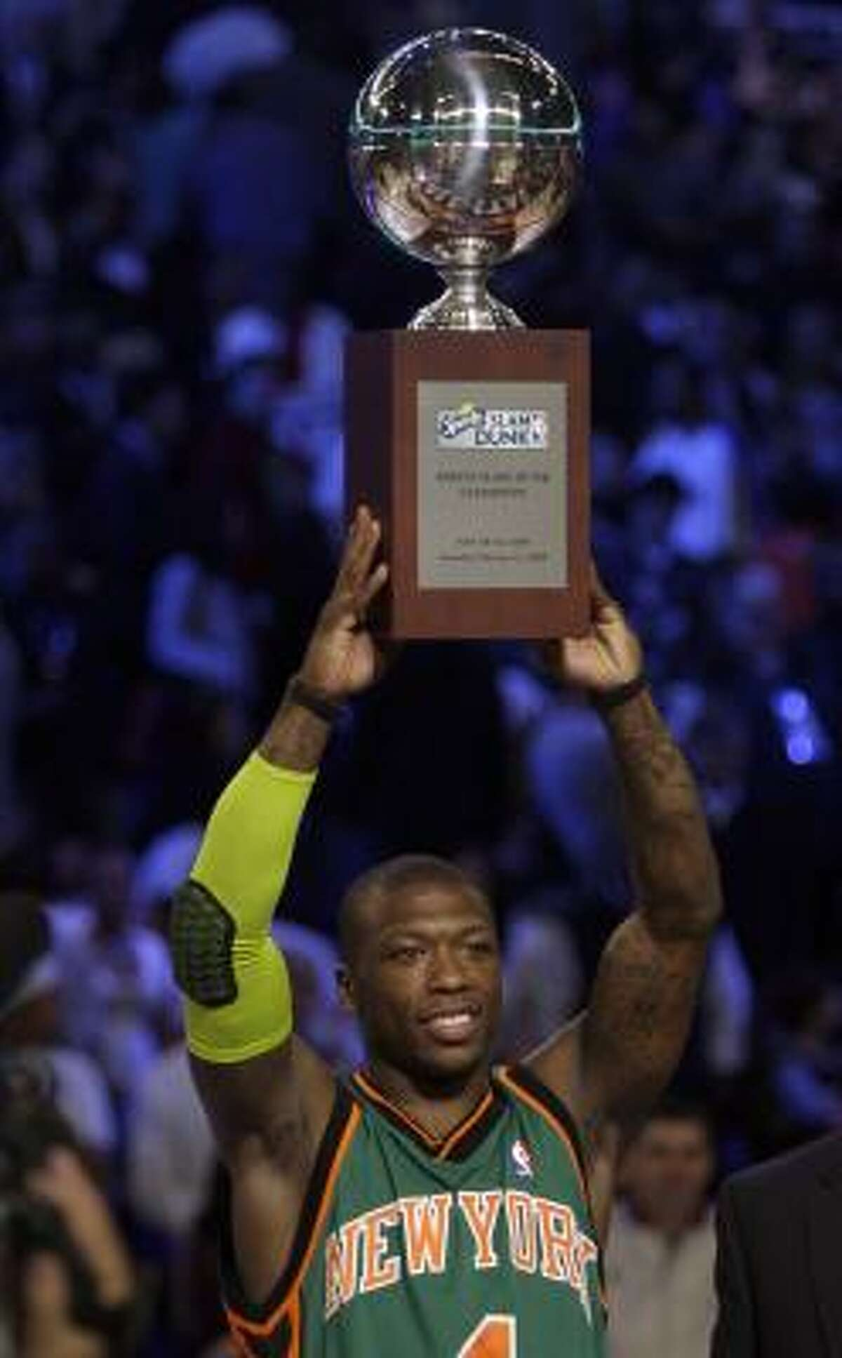 New York's Nate Robinson hoists his trophy after winning the slam dunk contest.