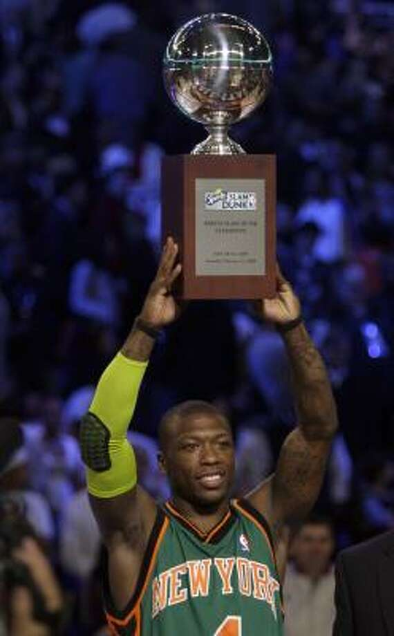 New York's Nate Robinson hoists his trophy after winning the slam dunk contest. Photo: Matt York, AP