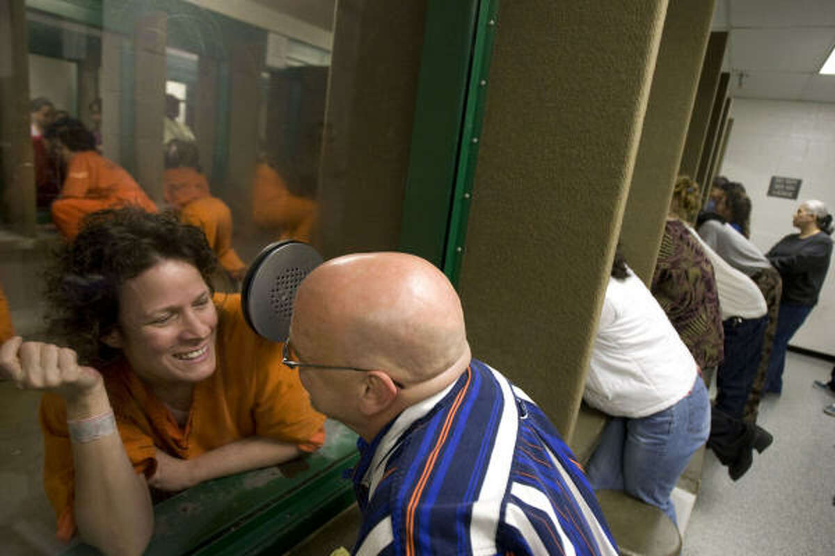 Ursula Tucker talks with her boyfriend, Brad Dean, through glass at the Harris County Jail facility on Valentine's Day .