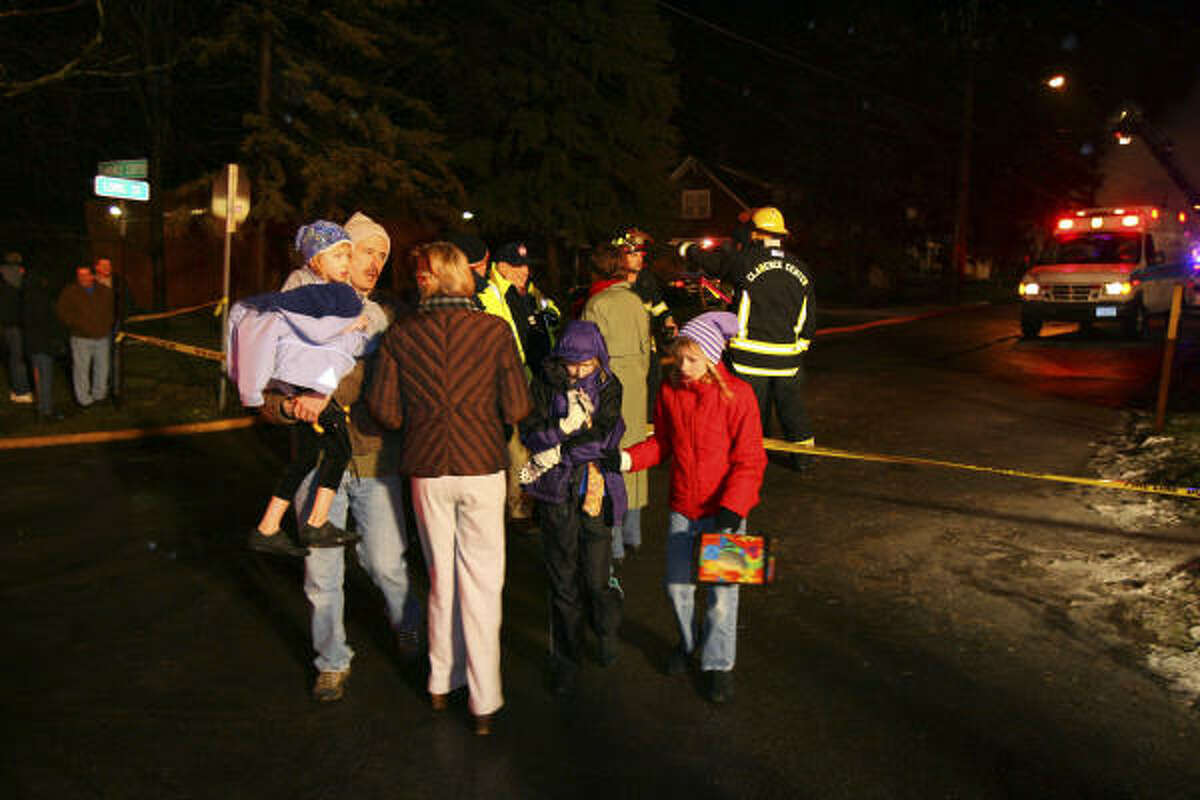 Families from surrounding homes are evacuated after the wreck of the commuter plane.