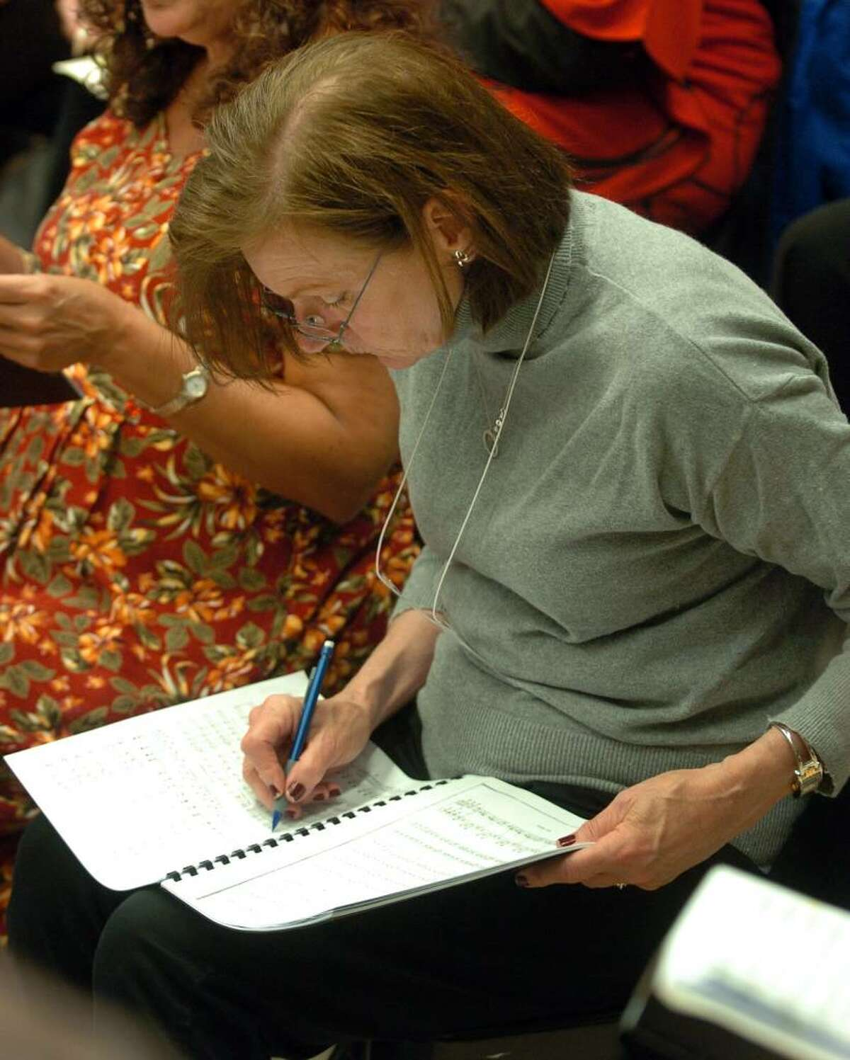 The Mendelssohn Choir rehearses at Staples High in Westpost, Conn. on Tuesday Sept. 29, 2009. Here, choir member Audrey Williams makes notations in her book during rehearsal of
