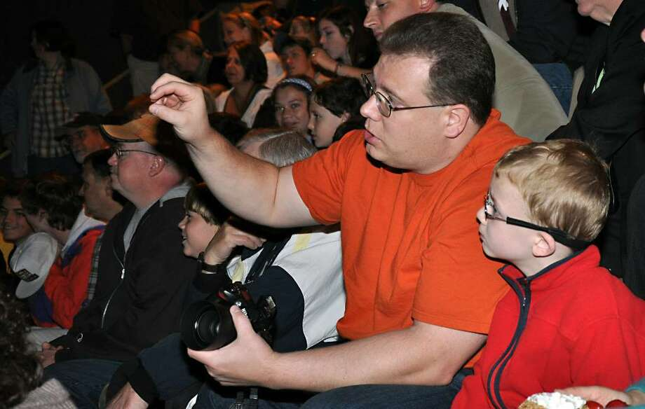 Timothy Webster and his son A.J., 6, of White Plains, watch intently as streaming video from NASA is projected in the auditoriuam of the Discovery Museum in Bridgeport on Friday, Oct. 9, 2009. The Discovery Museum is the only Connecticut LCROSS Observation Station listed on NASA's website. Photo: Amy Mortensen / Connecticut Post