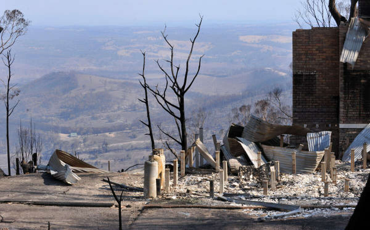 A view across the torched landscape in Phesant Creek on Thursday. Arsonists lit a wildfire that killed 21 people in Australia and are suspected of starting another that razed a whole town and may have left up to 100 dead, police said.