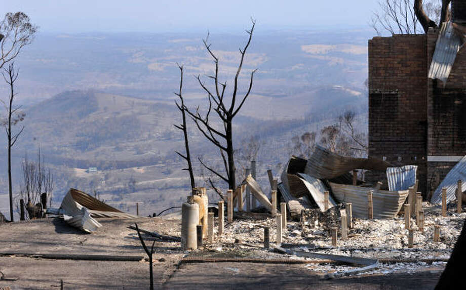 A view across the torched landscape in Phesant Creek on Thursday. Arsonists lit a wildfire that killed 21 people in Australia and are suspected of starting another that razed a whole town and may have left up to 100 dead, police said. Photo: PAUL CROCK, AFP/Getty Images