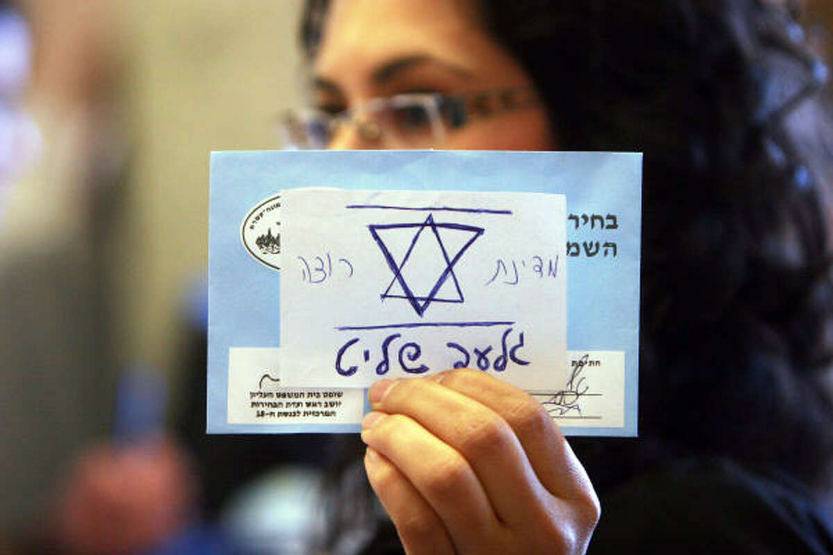 An Israeli election official holds up an invalid general election ballot with a note glued to it that reads in Hebrew: