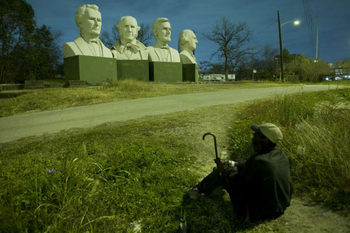 A man sits on the roadside across from David Adickes' busts, nicknamed
