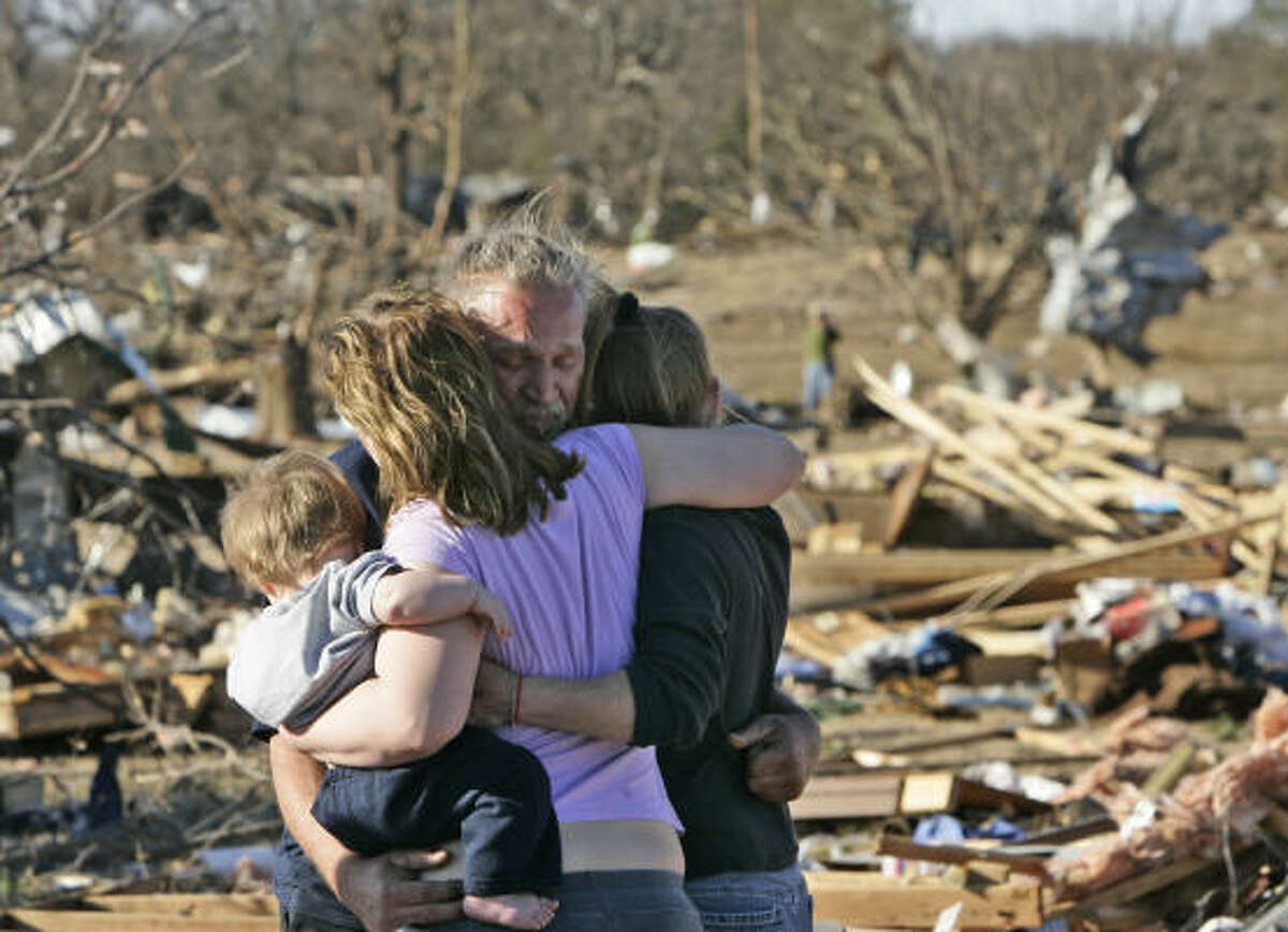 Dennis Parker is embraced by his daughter Dondria Hickman, left, who holds his grandson Benjamin Bryce Hickman, and friend Barbie Vaughn, right, in Lone Grove, Okla.