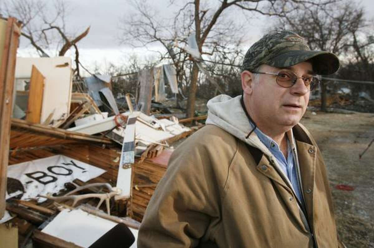 John Taliaferro sees the remains of his furniture store in first light after Tuesday's deadly tornado in Lone Grove, Okla. on Wednesday.