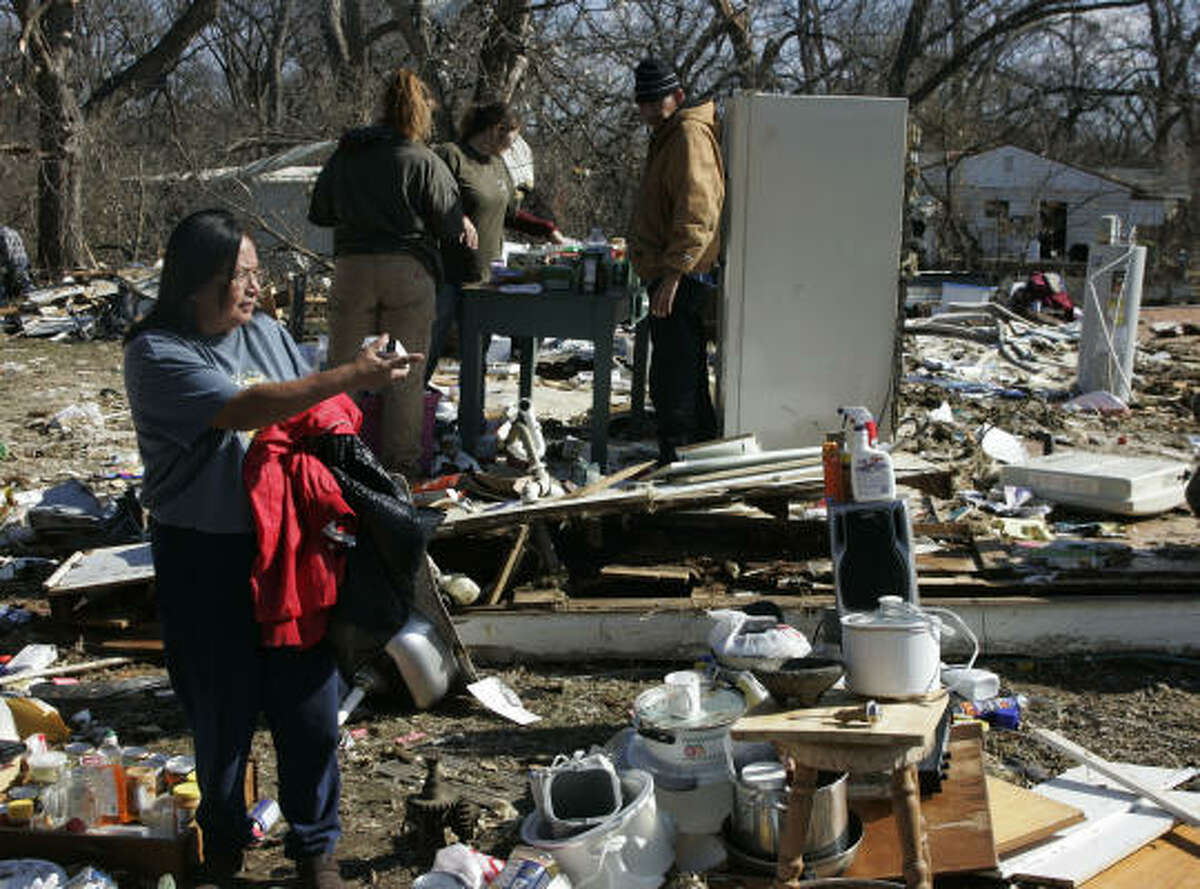 Shirley Mose surveys the damage to what was once her home in Lone Grove, Okla., Wednesday as friends clean out the refrigerator at rear. Mose's home was destroyed by a tornado Tuesday night.