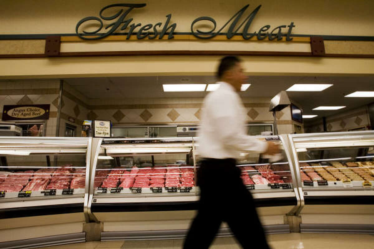 A customer passes the meat market at a Kroger in Houston. Many customers are buying their own steaks and other quality cuts of meat instead of going out to eat.