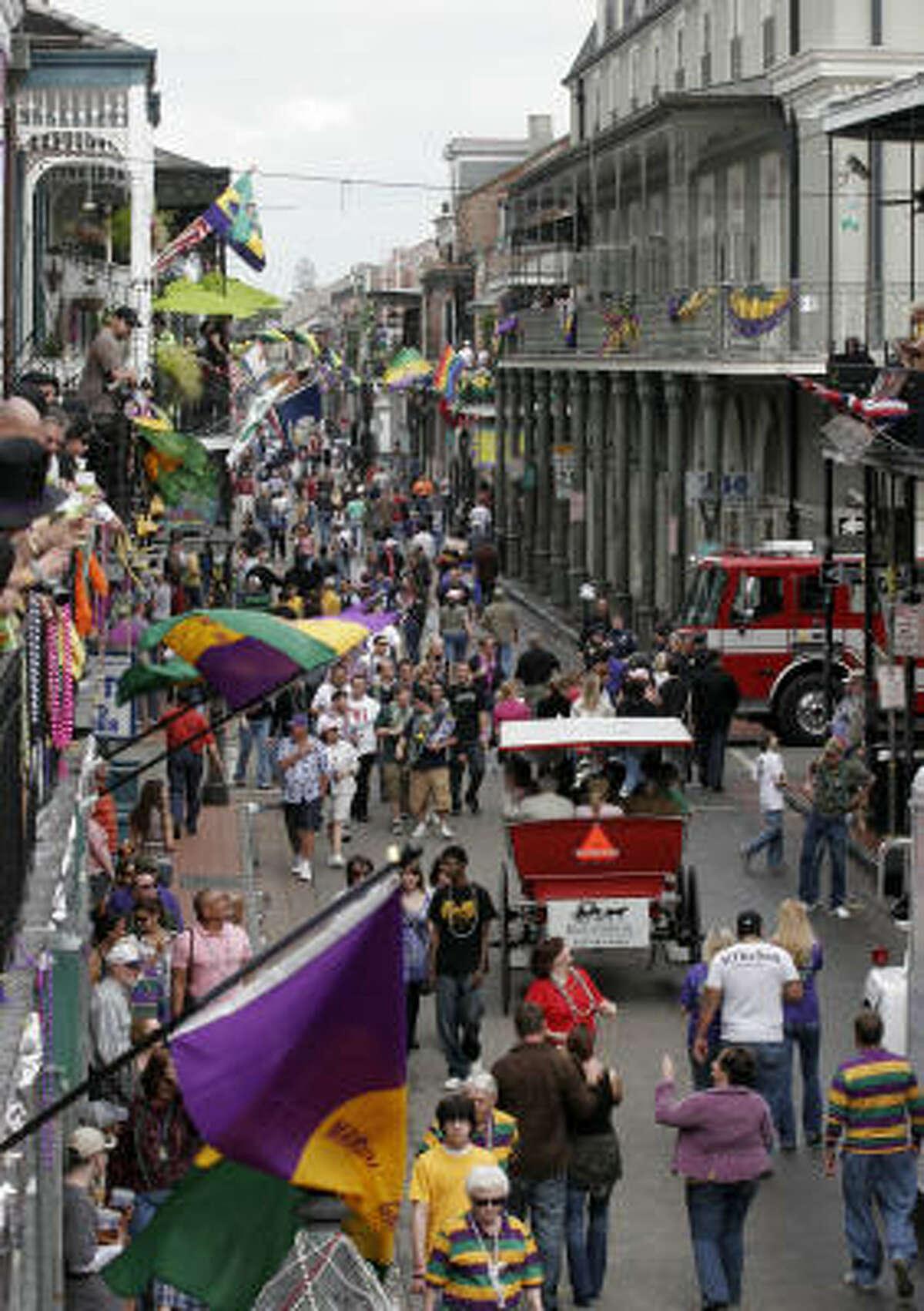 Mardi Gras revelers walk along Bourbon Street in the French Quarter of New Orleans.