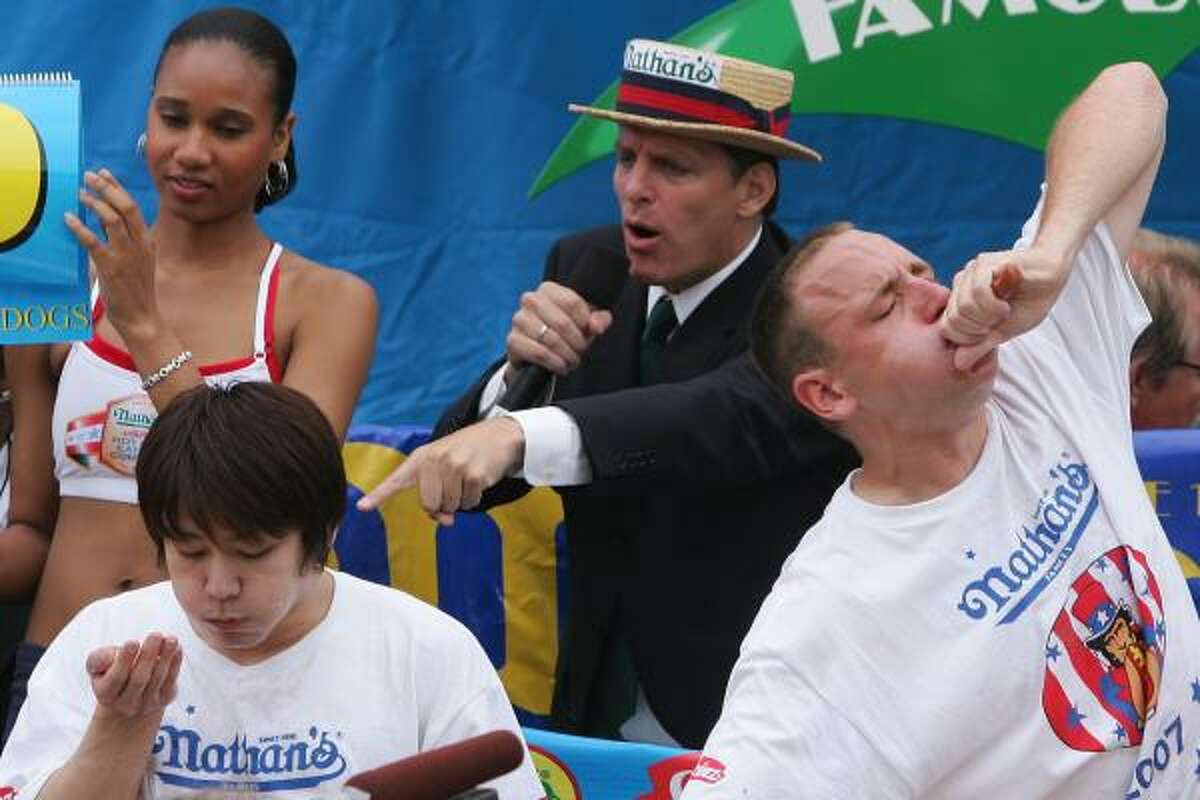 Takeru Kobayashi, left, and Joey Chestnut stuff hotdogs in their mouths during the annual hot dog eating contest at Coney Island July 4, 2007 in New York City.