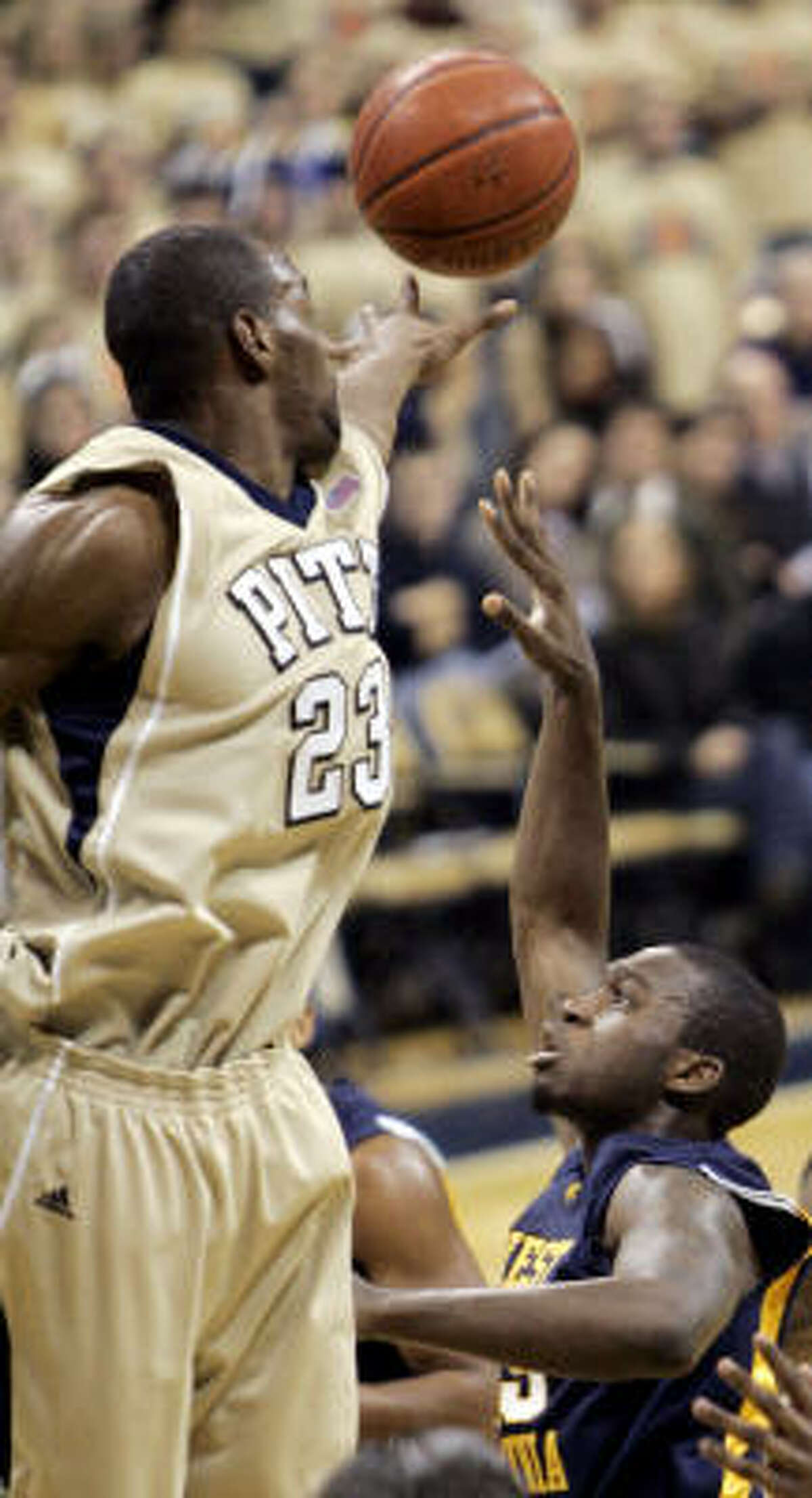Pittsburgh's Sam Young, left blocks a shot by West Virginia's Wellington Smith in the second half.