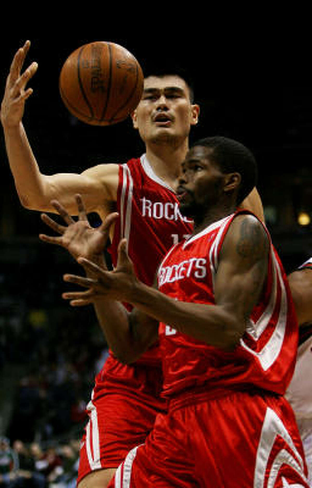 Rockets center Yao Ming, back, and teammate Aaron Brooks try to corral a rebound.