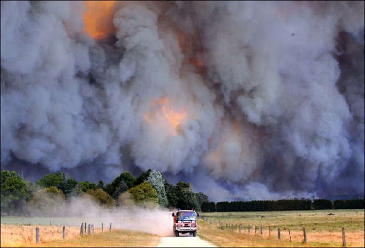IN AUSTRALIA An emergency vehicle races away from a blaze near a structure in the Gippsland region in Australia's Victoria state as raging wildfires swept southeastern Australia.
