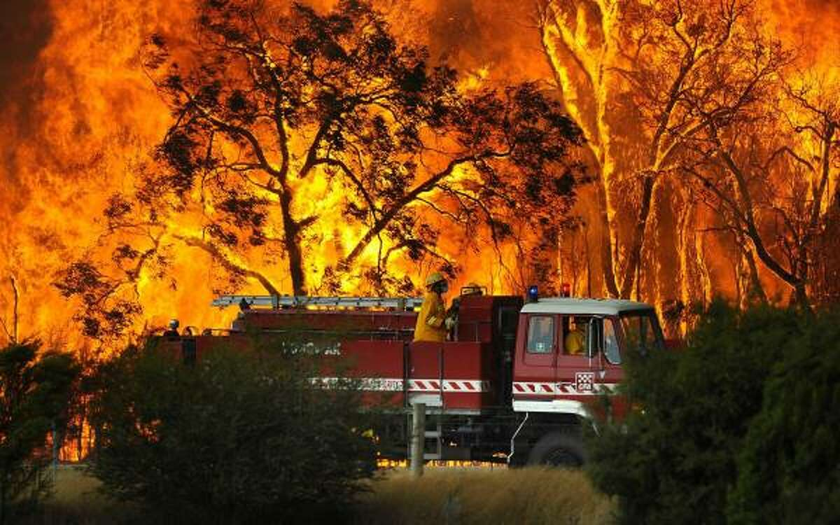 IN AUSTRALIA A fire truck moves away from out of control flames from a bushfire in the Bunyip Sate Forest near the township of Tonimbuk near Melbourne, Australia.