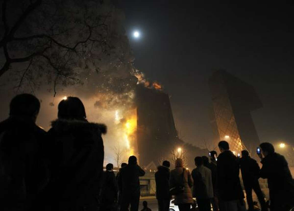 IN CHINA People gather to watch as unfinished Beijing hotel catches fire amid a holiday fireworks bonanza in Beijing on Monday.