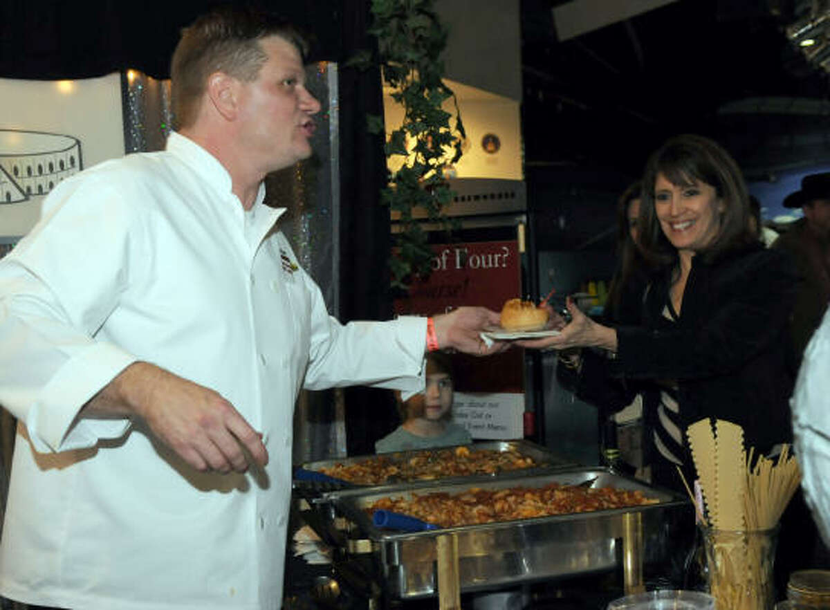 Colosseum Chief C.J. Johnston hands a plate of food to Norma Klouda.