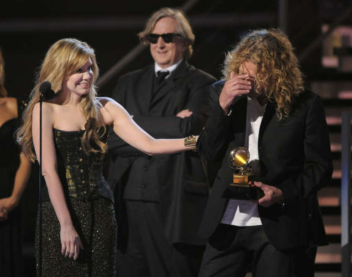 Alison Krauss, left and Robert Plant accept the award for album of the year. In background is the album's producer T-Bone Burnett.