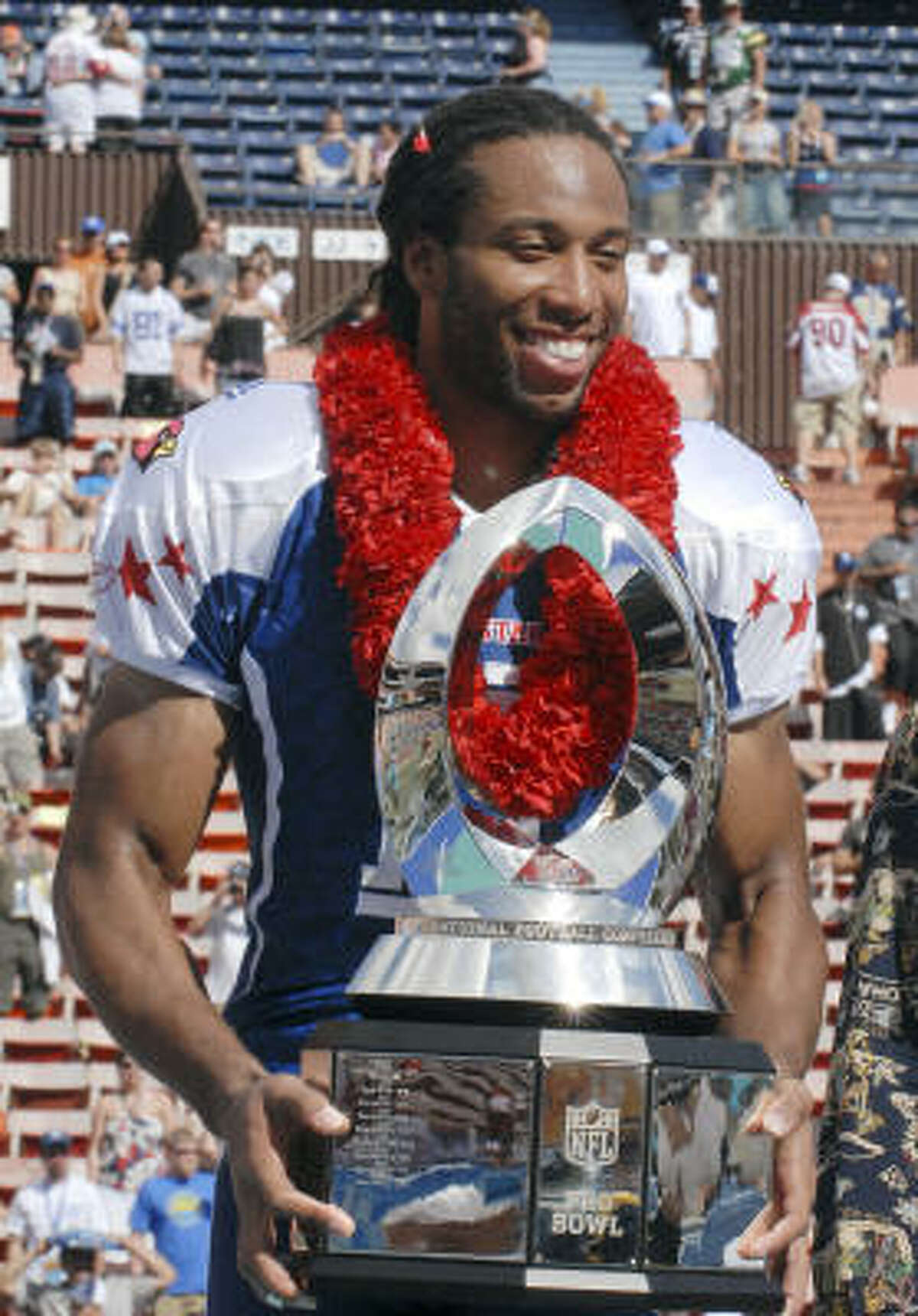 NFC receiver Larry Fitzgerald, of the Arizona Cardinals, holds the MVP trophy after the Pro Bowl. Fitzgerald caught five passes for 81 yards and two touchdowns.