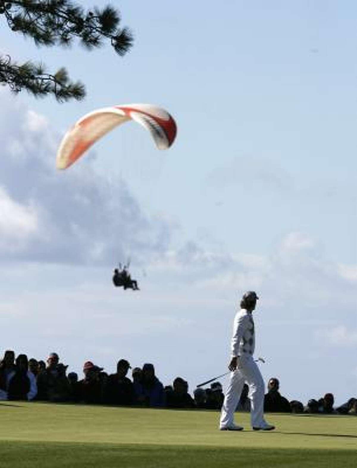 Camilo Villegas walks the 12th green as a glider floats overhead.