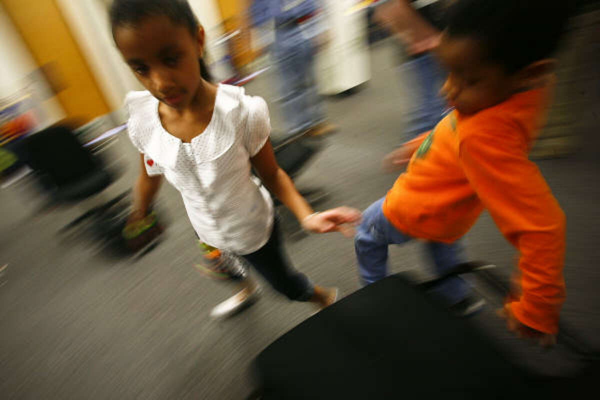 Amber Rivers-Whalen, 10, left, and brother Jonathan, 7, play musical chairs during the CPS Adoption Festival on Saturday, Feb. 7, 2009, in Houston.