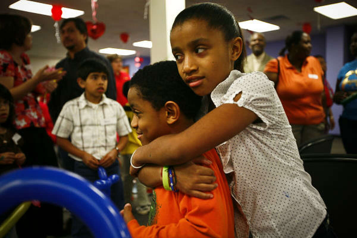 Jonathan Rivers-Whalen, 7, gets a hug from his sister Amber, 10, after playing a round of musical chairs during the CPS Adoption Festival on Saturday, Feb. 7, 2009, in Houston.