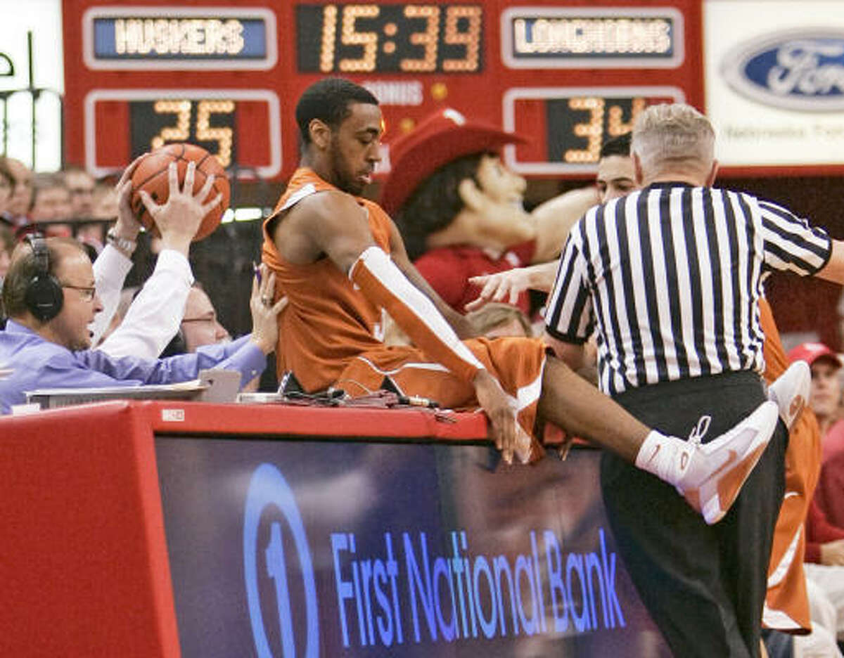 Texas' A.J. Abrams lands on the officials' table while going after a loose ball against Nebraska. Abrams finished with 16 points.