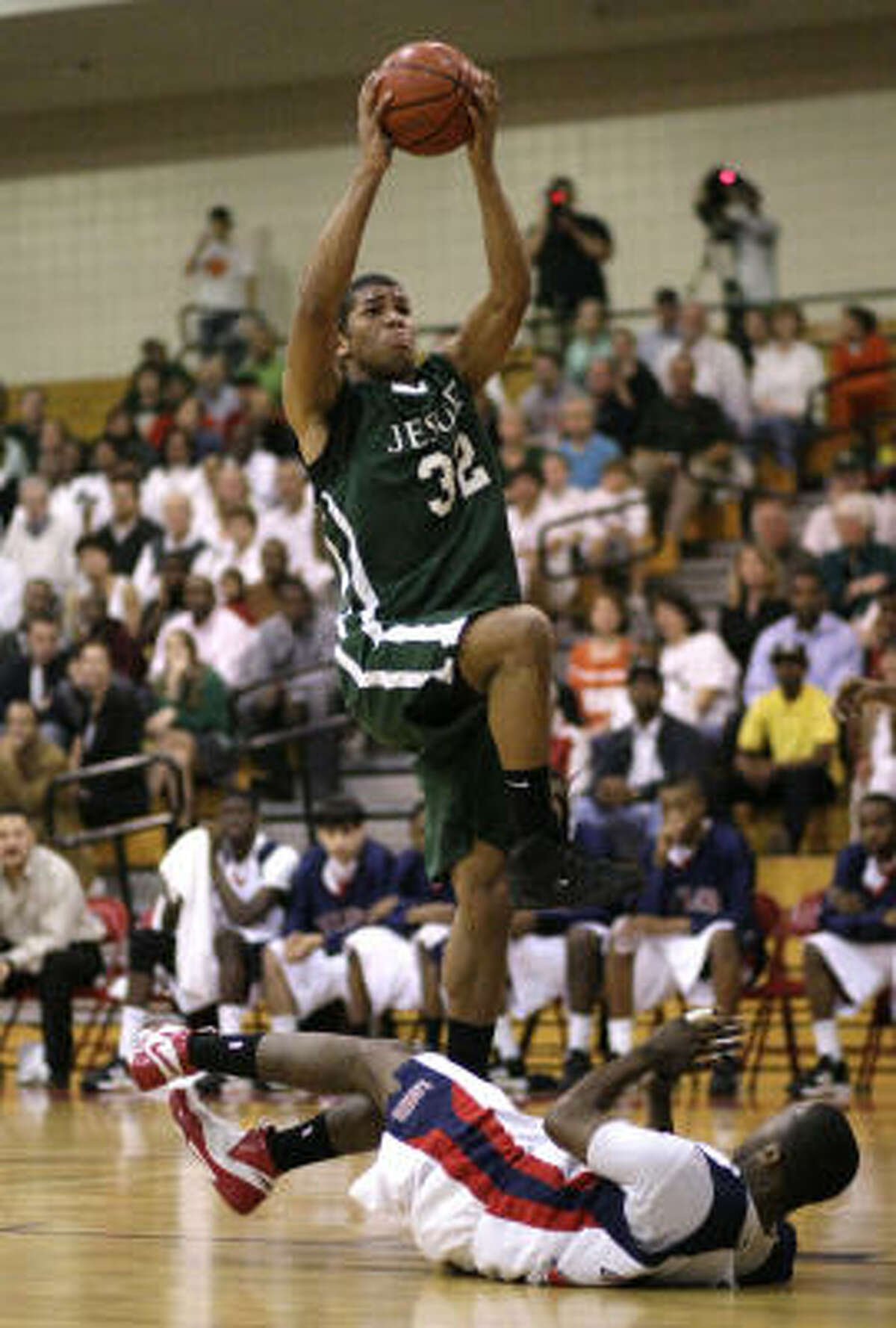 Strake Jesuit's Joey Brooks drives over Alief Taylor's Kendrick Murray for a layup in the first quarter.